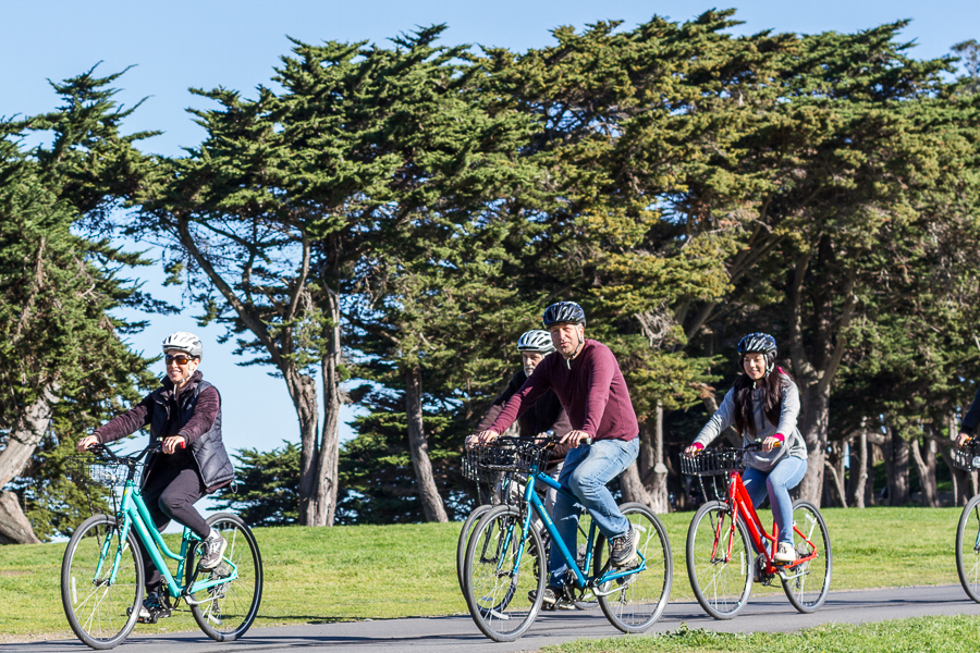 Guided bike tour riding through Fort Mason with cypress trees behind them, San Francisco