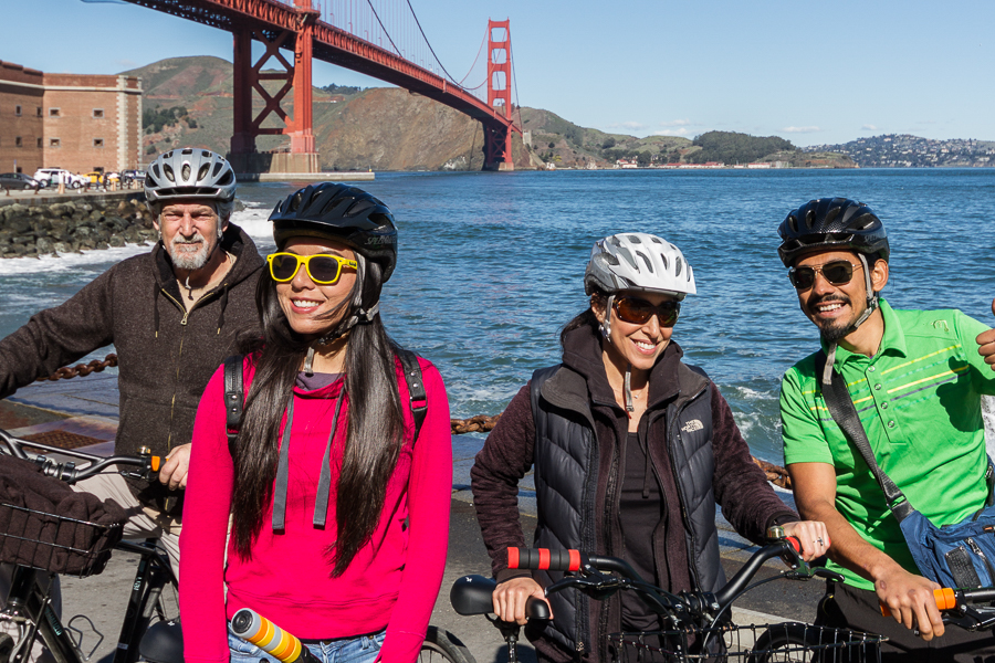 Group of cyclists standing near Fort Point with Golden Gate Bridge in background, San Francisco